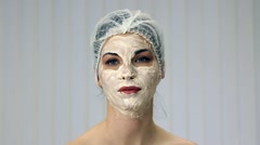 Relaxed woman with a deep cleansing nourishing face mask  - stock footage