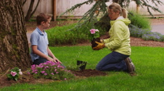 Mother and son planting flowers in yard. Shot on RED EPIC Stock Footage