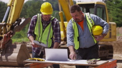 Construction workers looking at laptop computer Stock Footage