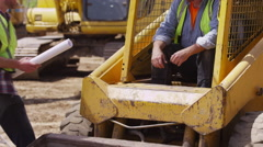 Excavators looking over plans Stock Footage