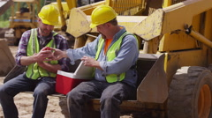 Two blue collar workers having lunch on job site - stock footage