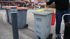 Man throwing away food waste into recycling bin on the street - stock footage