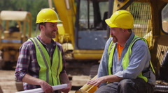 Two workers talking together on job site - stock footage