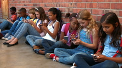 Stock Video Footage of Schoolchildren sitting outside using phones