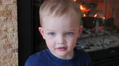 Boy by a fire in the living room dolly Stock Footage