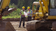 Two workers by excavation equipment look at blueprints - stock footage