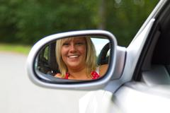 Woman looking in a Car Mirror Kuvituskuvat