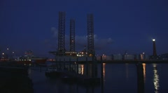 Offshore support vessel EDT Protea + Jackup rig + lighthouse by night Stock Footage
