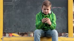 Teen Boy Sitting On Yellow Bench In Park And Talking At Mobile Phone, Outdoors Stock Footage