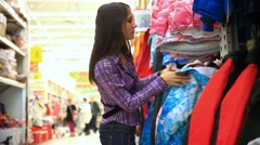 Young woman looks and trying at sport jacket in clothing store. HD. 1920x1080 Stock Footage