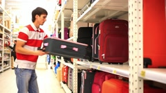 Beauty young man chooses suitcase in shop. HD. 1920x1080 Stock Footage