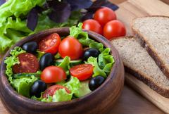 Healthy vegetarian salad with tomato and olives on rustic background - stock photo