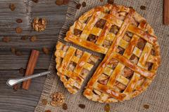 A piece of sliced apple pie with a metal spatula on vintage wooden background Stock Photos