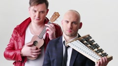 Two young men with musical instruments pose in white studio Stock Footage