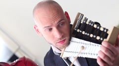 Handsome bald young man plays musical instrument in white studio Stock Footage