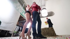 Dancing pair and man in background, in studio, filming a video clip Stock Footage