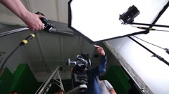 Camera and cameraman and male hands moving lights in studio Stock Footage