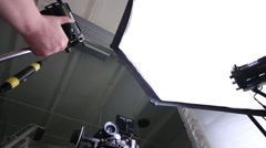 Camera and videographer and male hands moving lights in studio Stock Footage