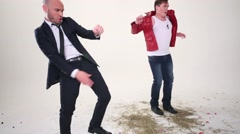 Bald man in suit and man in red jacket dance on floor with hay Stock Footage