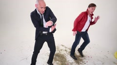 Man in suit and man in red jacket dance in white studio Stock Footage