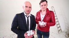 Bald young man in suit and man in red jacket throw small balloons Stock Footage