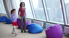 Little girl and woman walk near bag chair and big windows - stock footage