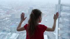 Back of little girl in red touching glass of window on rainy day - stock footage