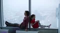 Woman and girl sit on windowsill of large window and talk Stock Footage