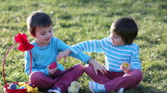 Two boys in the park, having fun with colored eggs for Easter, springtime Stock Footage