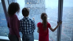 Mother, son and daughter look through large window with drops Stock Footage