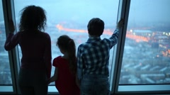 Mother with two children look at evening city through window - stock footage