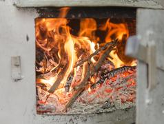 Distillation still Pot chamber fire-place burning wood branches with open door, Stock Photos