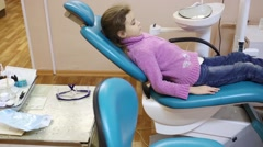 Little girl sits on dental operation chair in dental surgery Stock Footage