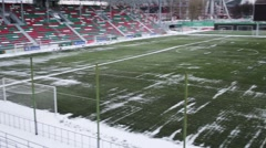 Green lawn and snow at small sports arena of stadium Stock Footage