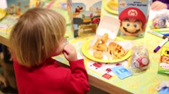 Boy in red eats in McDonalds in Moscow, Russia. Stock Footage