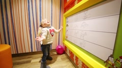 Little girl plays with balloons in colored room in McDonalds Stock Footage
