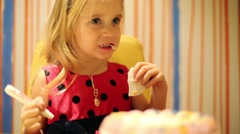 Little pretty girl in red dress eats confection at birthday - stock footage