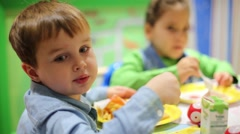 Little boy and girl eat cake by spoons at birthday. Focus on boy Stock Footage