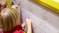 Two little girls and boy drawing on board  Stock Footage