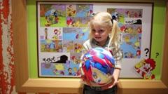 Little girl holds balloon near board with cartoon in McDonalds. - stock footage