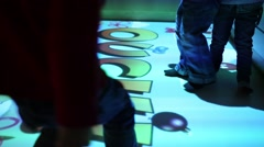 Legs of kids jumping and playing on interactive floor in room Stock Footage
