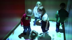 Five kids jump and play on interactive floor in room Stock Footage