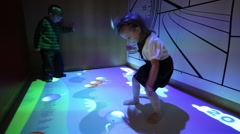 Little boy and girl jump and play on interactive floor in room - stock footage