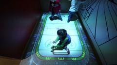 Kids play hockey in room with interactive floor in McDonalds. Stock Footage