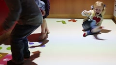 Three little children catch numbers on interactive floor in room Stock Footage