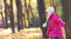 Two happy children run in autumn park with dry yellow leaves Stock Footage