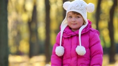 Cute little girl in pink claps her hands in park at autumn day Stock Footage
