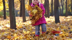 Cute little girl in pink throws leaves in park at autumn day Stock Footage