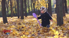Little boy with scoop goes on dried yellow foliage in autumn park Stock Footage