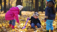 Three children play in autumn park with dry leaves. Stock Footage